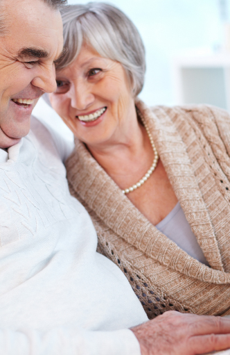 elderly woman smiling and leaning against elderly man