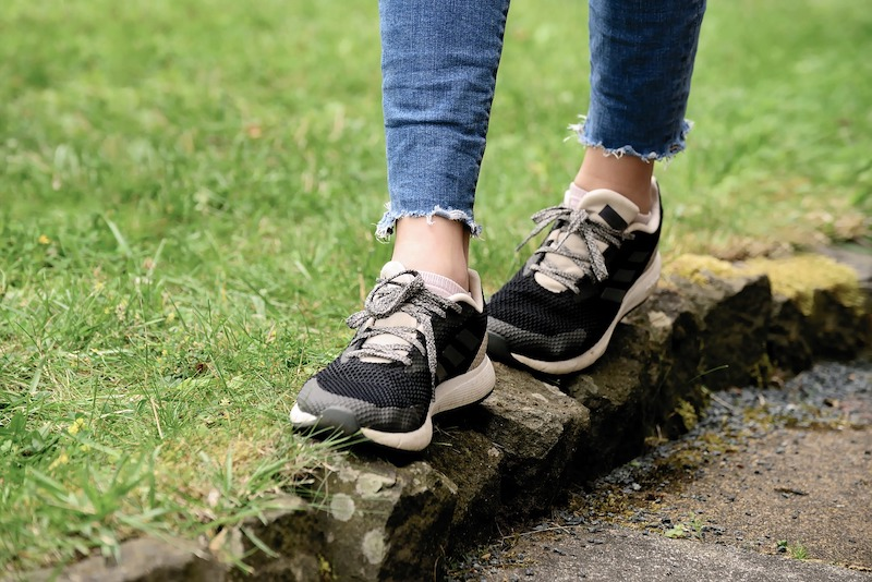 close up of person wearing sneakers and walking on narrow rocks