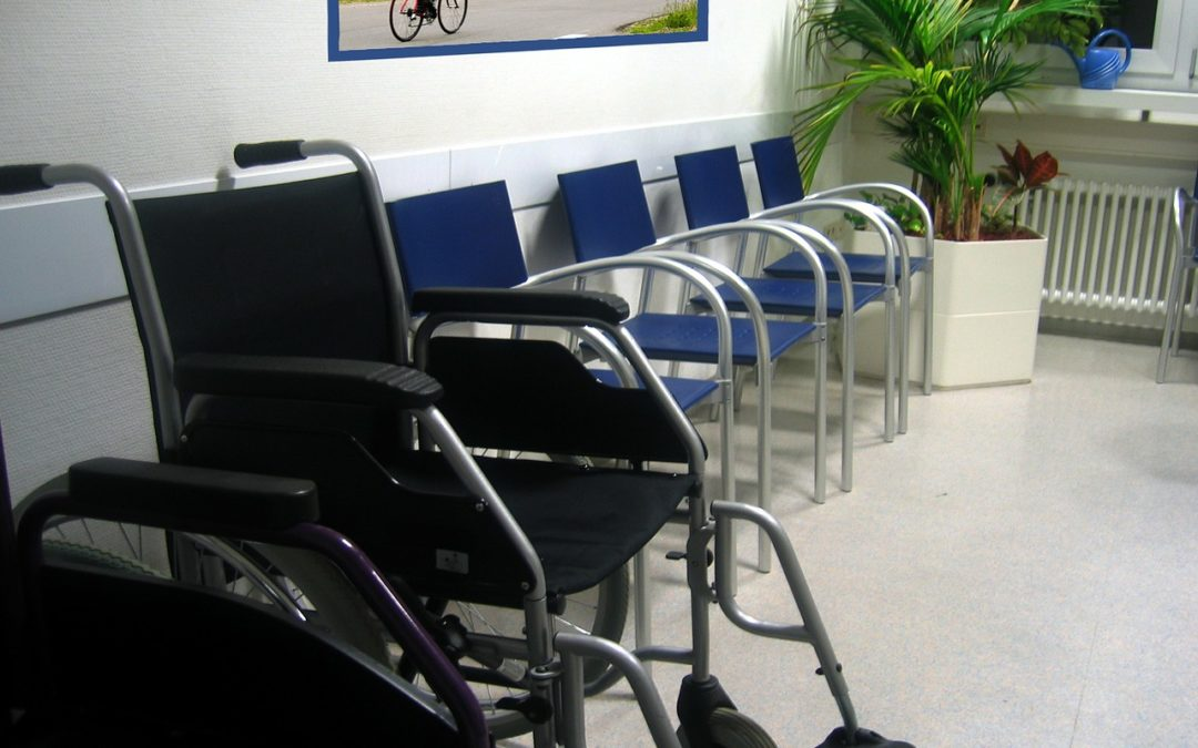 wheelchair next to line of chairs in doctor office waiting room